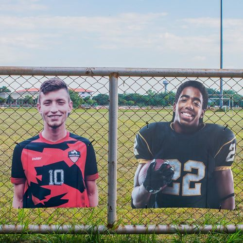 Sports player cutouts installed on fence